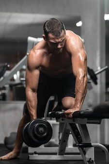 Hombre entrena en el gimnasio hombre atlético entrena con mancuernas, bombeando sus bíceps