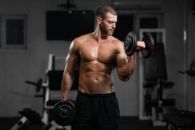 Hombre entrena en el gimnasio. hombre atlético entrena con mancuernas, bombeando sus bíceps.