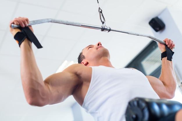 Hombre en entrenamiento deportivo trasero en gimnasio de fitness