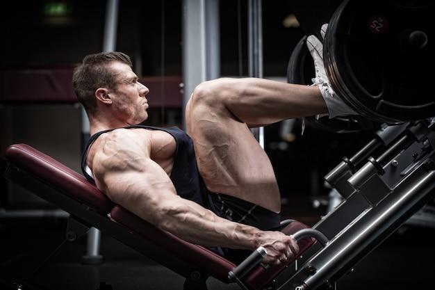Hombre en el entrenamiento de gimnasio en la prensa de piernas