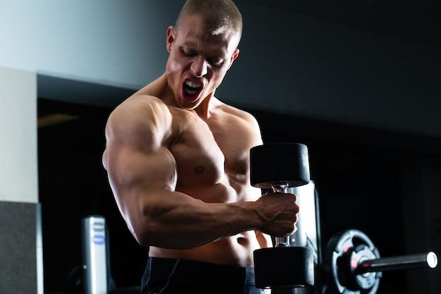 Hombre en entrenamiento con mancuernas en el gimnasio