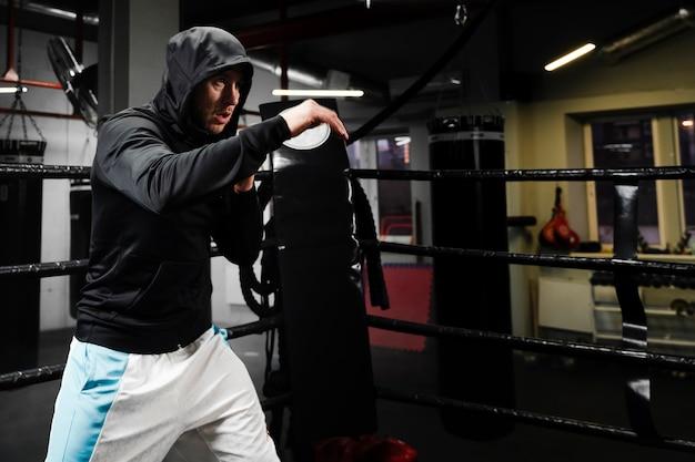 Hombre en entrenamiento de ropa deportiva en ring de boxeo con espacio de copia