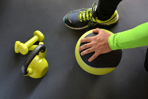 Hombre entrenando con kettlebell y balón medicinal en casa