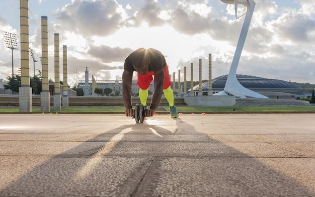 Hombre entrenando los músculos abdominales con una rueda en el parque