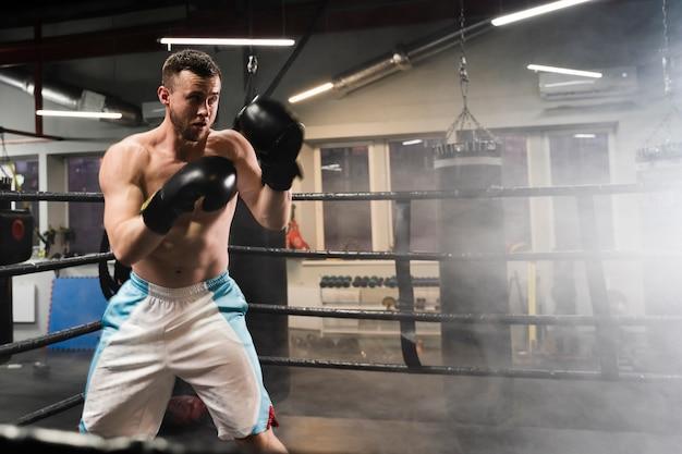 Hombre entrenando en ring de boxeo