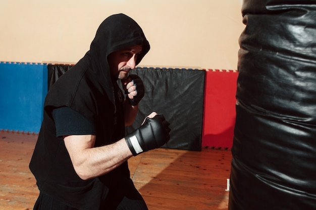 Hombre entrenando con saco de boxeo en el gimnasio