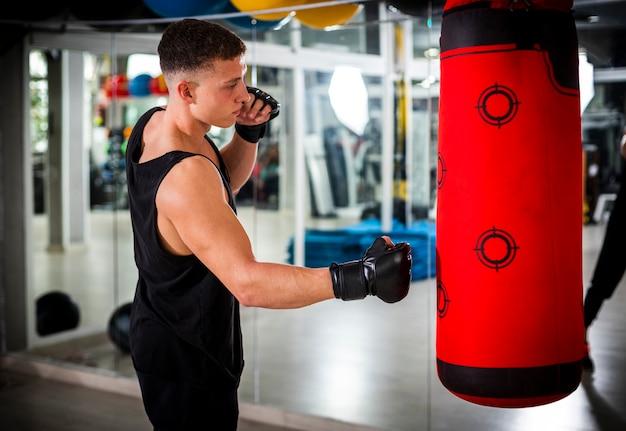 Hombre entrenando con saco de boxeo