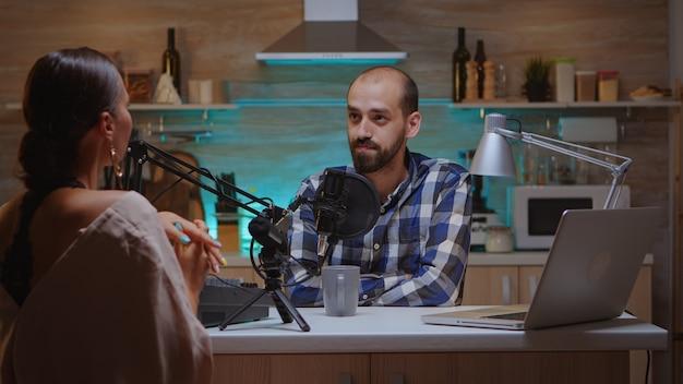 Hombre entrevistando a mujer vlogger en home studio para podcast. espectáculo creativo en línea producción al aire, presentador de transmisión por internet, transmisión de contenido en vivo, grabación de comunicación digital en redes sociales