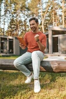 Hombre entusiasta con tableta sentado en la naturaleza
