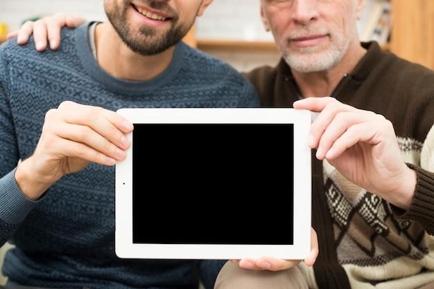Hombre envejecido abrazando chico joven y mostrando tableta