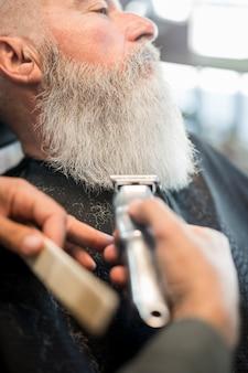 Hombre envejecido con barba larga y gris en barbería para recortar