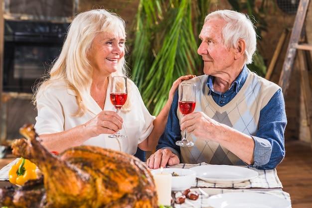 Hombre envejecido y mujer con gafas en la mesa