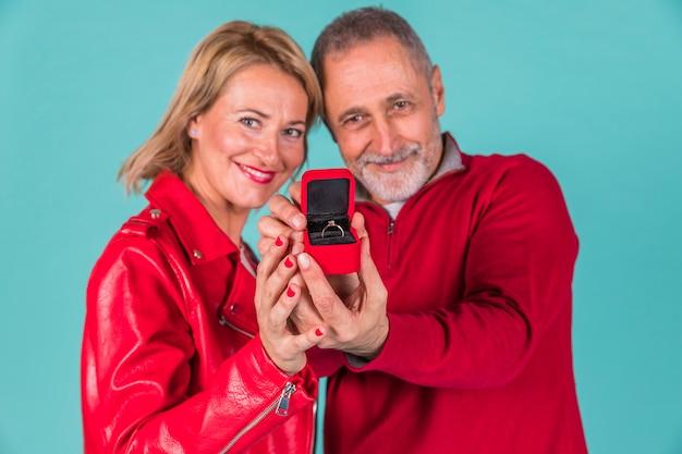 Hombre envejecido y mujer positiva mostrando caja de joyas