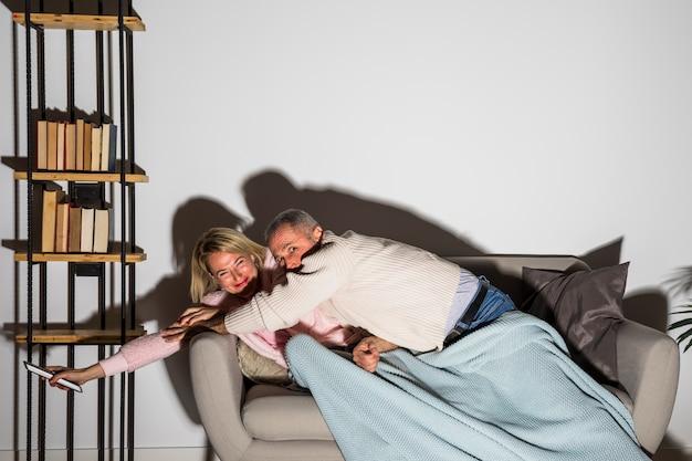 Hombre envejecido que detiene a la mujer sonriente con el control remoto de la tv para cambiar el canal en la tv en el sofá