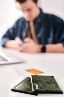 El hombre envía un mensaje de texto mientras se prepara para el viaje en segundo plano, se centra en los pasaportes en los casos verdes en la mesa