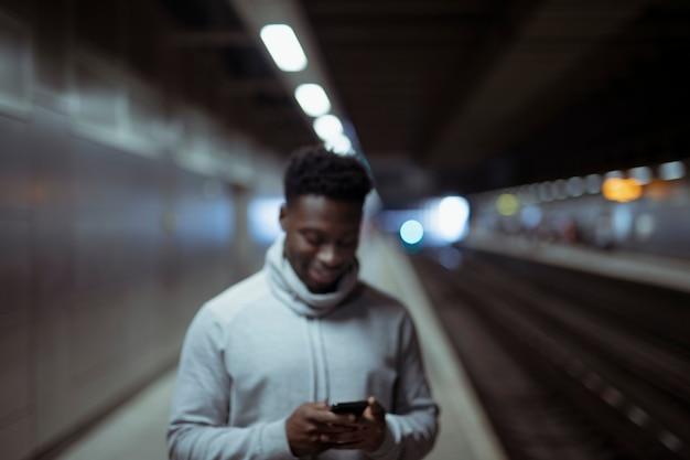 Hombre enviando mensajes de texto en una estación de metro