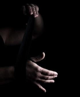 Hombre envuelve sus manos en venda textil negra para deportes.