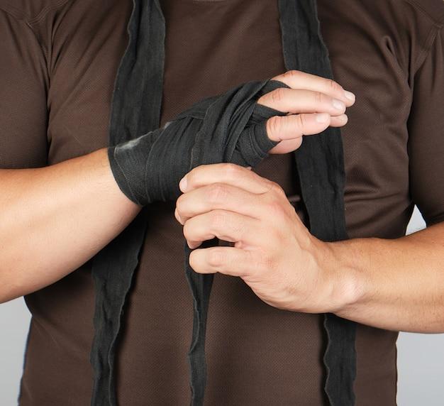 El hombre envuelve sus manos en vendaje textil negro para deportes, blanco