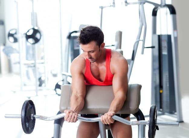Hombre con equipo de entrenamiento con pesas en gimnasio de deporte