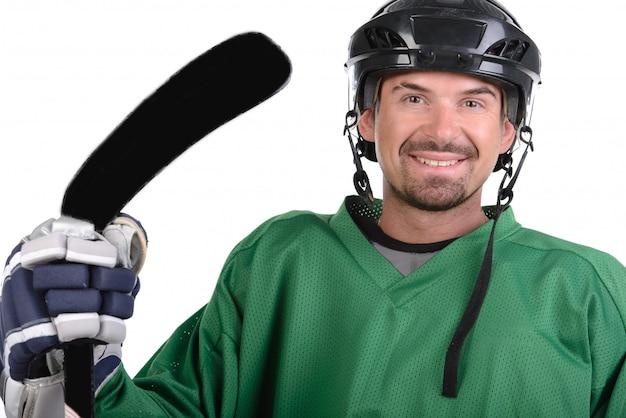 Un hombre en equipo está parado y sosteniendo un palo cerca de él.