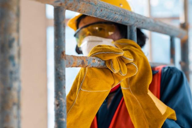 Hombre con equipo de seguridad vista lateral llevando escalera cerrar