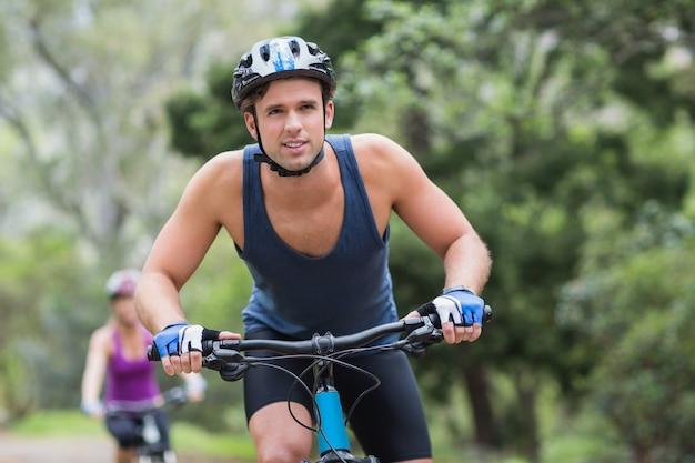Hombre, equitación, ciclismo, en, sendero, en, bosque