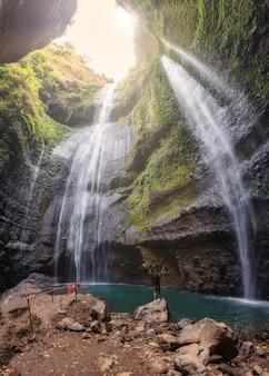 El hombre es feliz en las rocas en la cascada de madakaripura en el fondo de la selva tropical