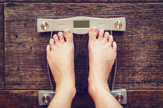 Hombre en la escala de peso en el piso de madera, concepto de dieta.
