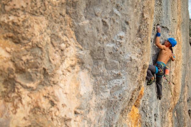 Hombre escalador sin camisa escalar la pared de la montaña en un increíble día soleado