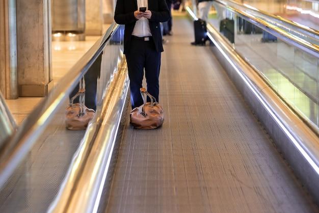Hombre en escaleras mecánicas en el aeropuerto mediante teléfono móvil con equipaje