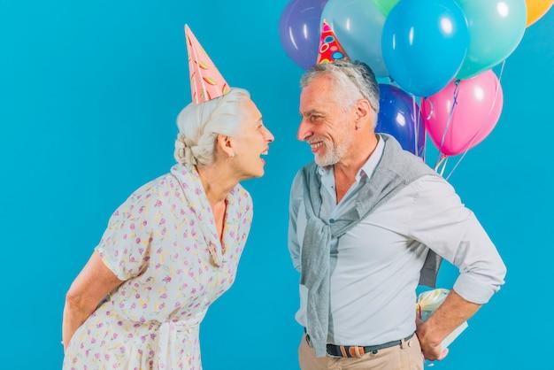 Hombre escondido regalo de cumpleaños de su esposa sobre fondo azul