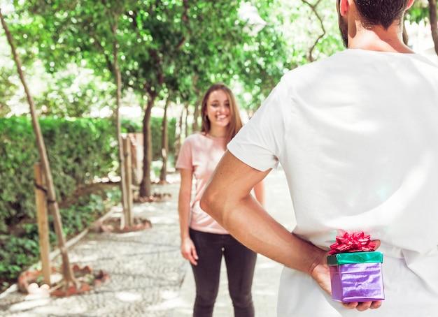 Hombre escondiendo el regalo de su novia en el parque