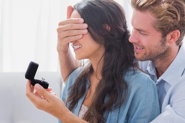 Hombre escondiendo los ojos de su esposa para ofrecerle un anillo de compromiso