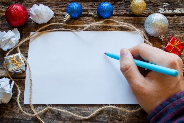 El hombre escribe una lista de regalos para el año nuevo.