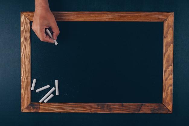 Hombre escribiendo algo con vista superior de tiza en un marco y negro