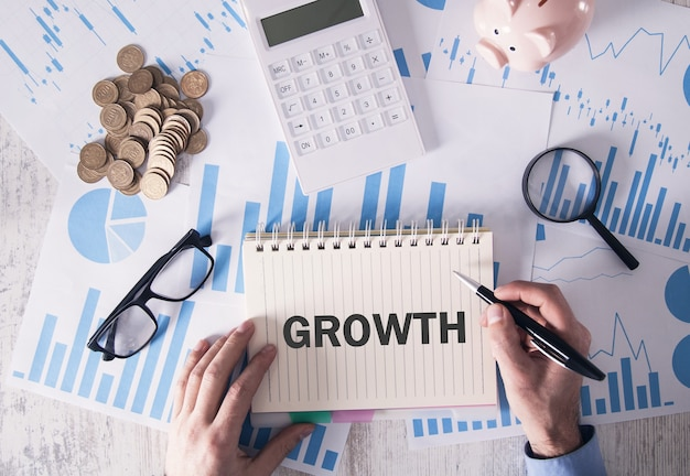 Hombre escribiendo en el bloc de notas. crecimiento. concepto de negocio