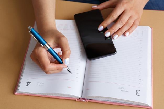 Hombre escribiendo con bolígrafo en el diario y sosteniendo el teléfono inteligente en la mano