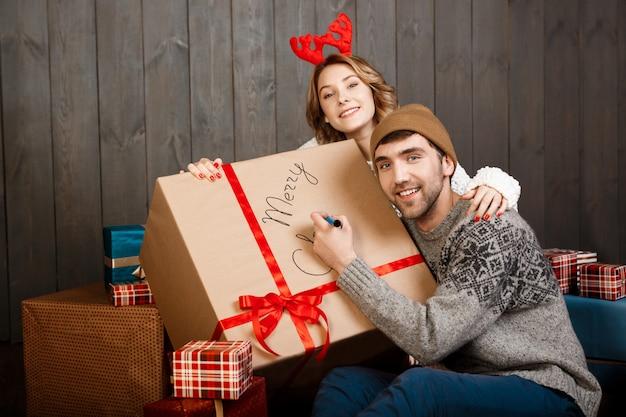 Hombre escribiendo en caja de regalo feliz navidad sentado con novia.