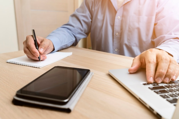 Hombre escribiendo en la computadora portátil y escribiendo