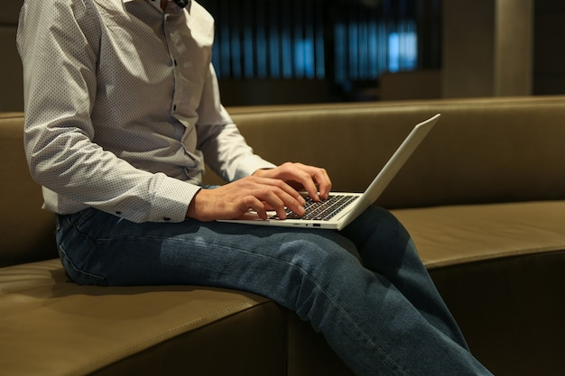 Hombre escribiendo en la computadora portátil en el hotel de cerca