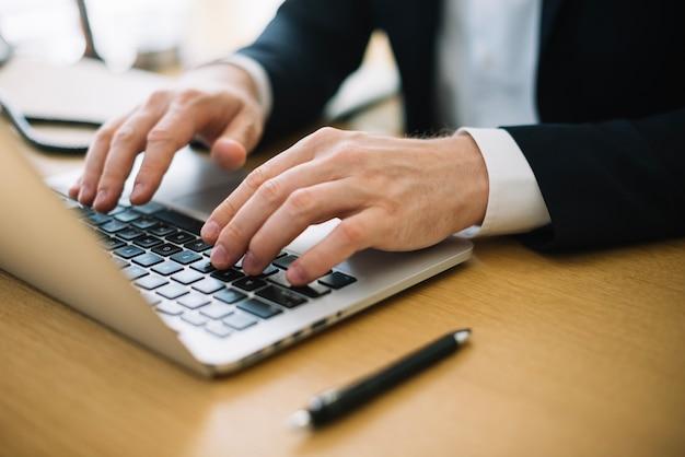 Hombre escribiendo en la computadora portátil en la oficina