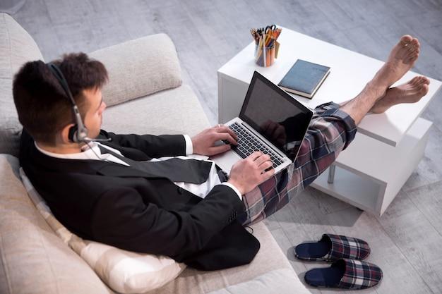 Hombre escribiendo en computadora portátil trabajando en casa independiente.