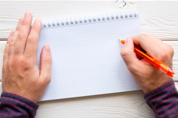 Hombre escribiendo en un cuaderno, lugar para texto