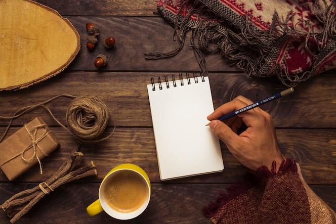 Hombre escribiendo en el elegante lugar de trabajo de otoño