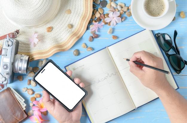 Hombre escribiendo en el libro del planificador y sostenga el teléfono móvil