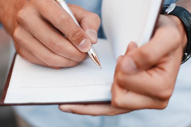 Hombre escribiendo notas en un bolígrafo de explotación de mano de cuaderno
