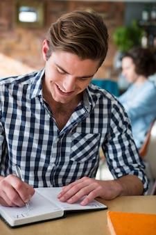 Hombre escribiendo notas en el diario en la cafetería.