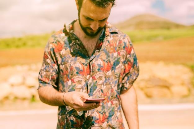 Hombre escribiendo en la pantalla del teléfono móvil al aire libre