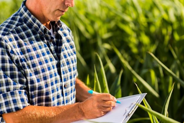 Hombre escribiendo en un portapapeles al aire libre
