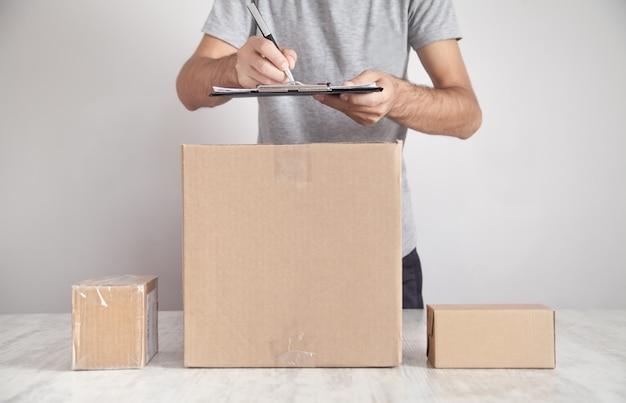 Hombre escribiendo en portapapeles. cajas de cartón en el escritorio.